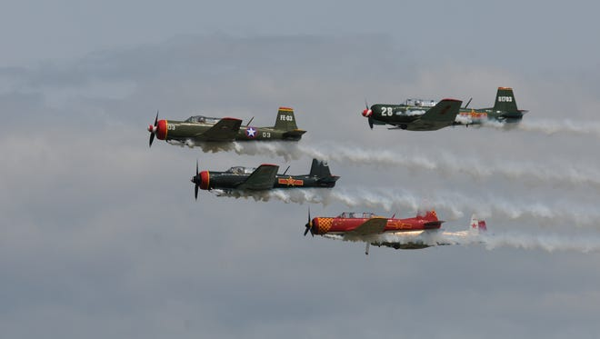 Various Warbirds  perform during the AirVenture 2014 air show on the first day of the convention in Oshkosh, Wisconsin.