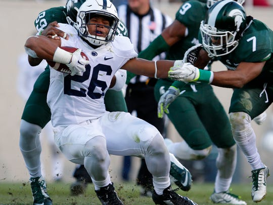 Penn State running back Saquon Barkley, center, is stopped by Michigan State's Shilique Calhoun, left, and Demetrious Cox, right, during the second quarter of Saturday's game in East Lansing, Mich. Michigan State won, 55-16.