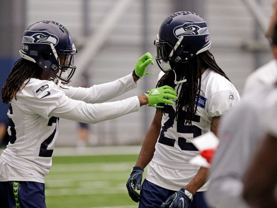 Seahawks cornerback Richard Sherman, right, offers