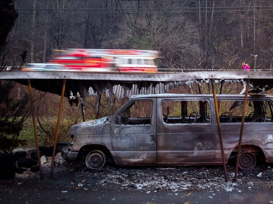 Fire engines pass by a burned out van on U.S. Highway