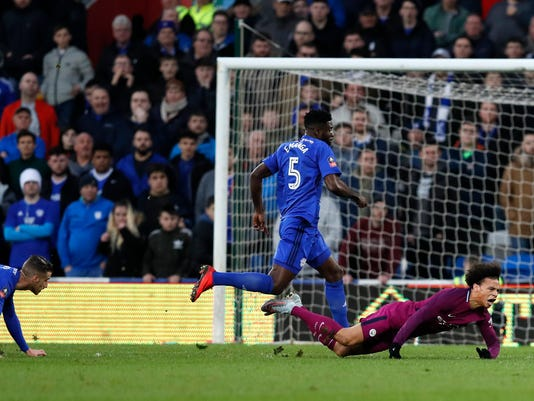 Manchester City's Leroy Sane, right, falls after being fouled by Cardiff City's Joe Bennett, left, during the English FA Cup fourth round soccer match between Cardiff City and Manchester City at Cardiff City stadium in Cardiff, Wales, Sunday, Jan. 28, 2018. (AP Photo/Kirsty Wigglesworth)