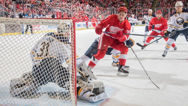 Detroit center Dylan Larkin tries to get the puck past Buffalo goalie Chad Johnson in the first period.