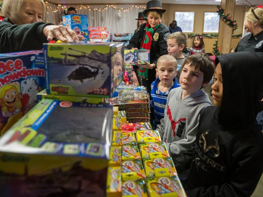 Kids line up to pick out Christmas presents at the annual Evansville FOP Christmas party on Saturday morning.