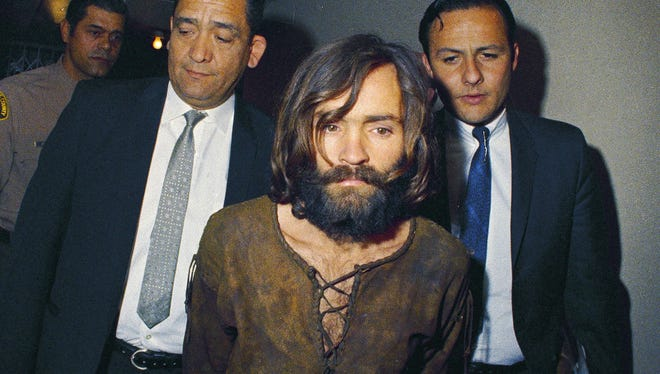 In this 1969 file photo, Charles Manson is escorted to his arraignment on conspiracy-murder charges in connection with the Sharon Tate murder case. The cult leader and mastermind behind 1969 deaths of actress Sharon Tate and others died on Nov. 19, 2017. He was 83.