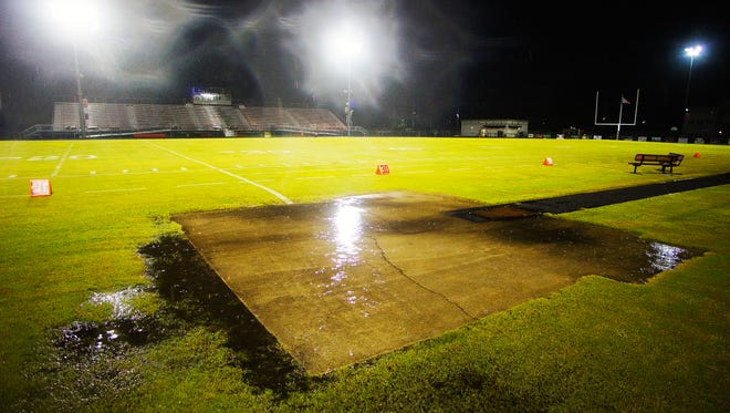 Water pools on the football field at South Fort Myers High School last Friday. South's game against Island Coast was one of many area football games cancelled due to rain and lightning.