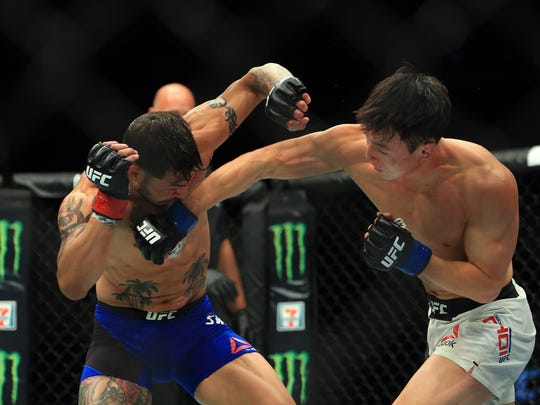 Doo Ho Choi (R) lands a punch on Cub Swanson in their Featherweight bout during the UFC 206 event at Air Canada Centre on Dec. 10, 2016.