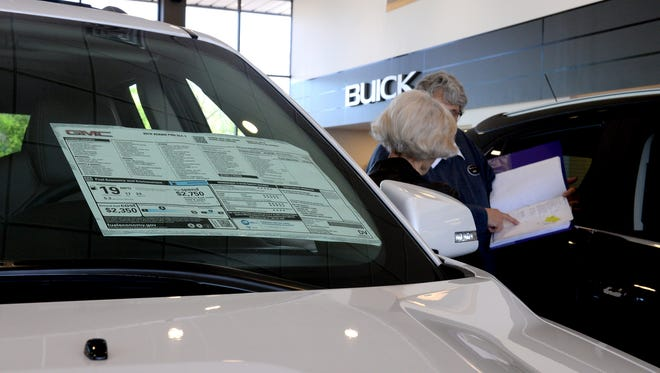 A customer shops for a car inside the showroom at Glenn Buege Buick GMC Monday in Lansing as the window sticker for a 2016 GMC Acadia is displayed on the windshield. General Motors has told dealers not to sell about 60,000 of its hit-selling 2016 large crossovers -- Chevrolet Traverse, GMC Acadia and Buick Enclave -- because their Monroney stickers overstate the vehicles' fuel economy ratings.