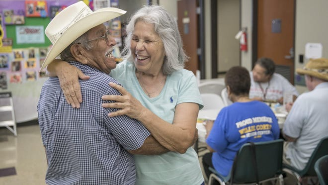 Volunteer Elsa Solis, right, a retired state social worker, greets Robert Maldonado last fall at the Willie M. Cortez Senior Center in San Antonio. Social Security has provided a safety net for generations of retirees.
