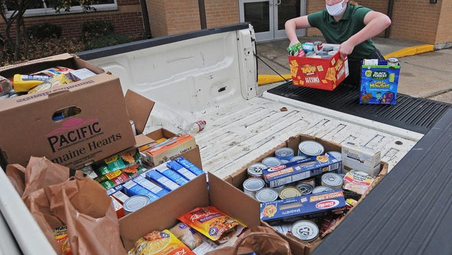 Edyn Schapton, 11, loads donated food items collected by St. Mary's Grade School and and donated to the Salina Emergency Aid Food Bank and Catholic Charities of Northern Kansas into a truck. The school surpassed their goal of collecting over 1,000 cans.