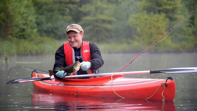 Larry Keen of Waunakee admires a largemouth bass he caught while fishing from his kayak in Iron County.