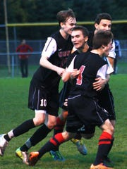 Livonia Churchill's Erlin Guri (facing camera) is congratulated by teammates after scoring the utlimate game-winning goal Wednesday night against Plymouth.
