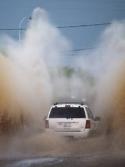 A car navigates floodwaters from a monsoon storm in