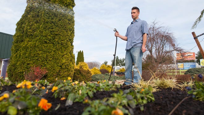 "Josh Waldron, who co-owns Waynesboro Golf and Games with his wife, waters plants beside the miniature course on Thursday, April 2, 2015. Waldron left a job as a social studies teacher at Waynesboro High School to run the business. ""Former students are some of my best customers,"" he said. "" Some of them helped renovate this place."""