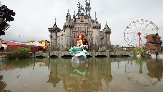"""In this Aug. 20, file photo,  a view of 'Dismaland' , in Western-super-Mare, Somerset, England.  An anarchic amusement park by street artist Banksy that mocked capitalism and consumer culture has brought an economic boom to a faded seaside town. Banksy's Dismaland """"bemusement park"""" transformed a derelict outdoor swimming pool in Weston-Super-Mare into a macabre parody of a theme park, complete with a derelict castle, a dead Cinderella and a Grim Reaper in a bumper car. Local officials say the attraction, which closes Sunday, Sept 27, after five weeks, drew more than 150,000 people to the southwest England town of 75,000."""