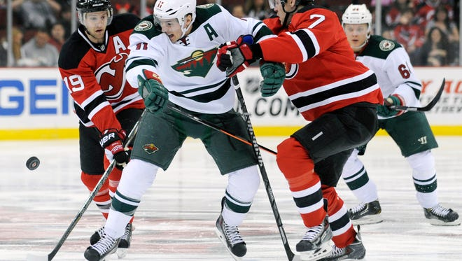 The Minnesota Wild's Zach Parise is sandwiched by the New Jersey Devils' Travis Zajac, left, and Mark Fayne, right, during Thursday night's game.