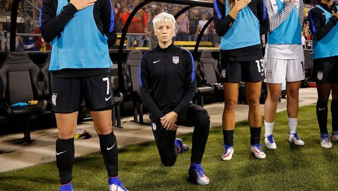 Megan Rapinoe kneels during the national anthem.