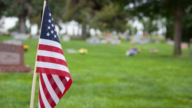 In preparation for Memorial Day, Residents of Washington City gather to place flags on veteran graves at the Washington City Cemetery Saturday, May 23, 2015.