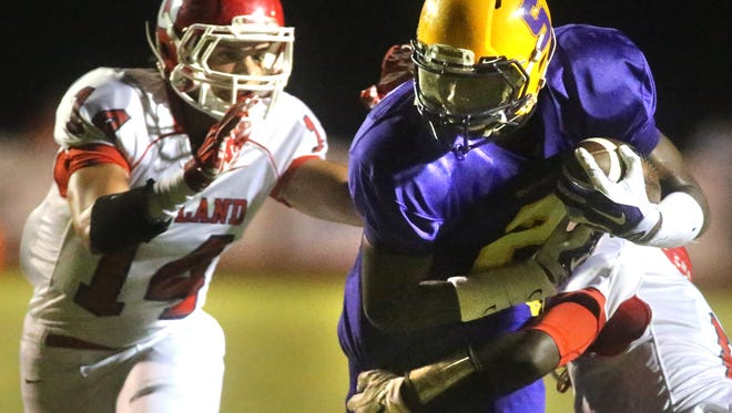 Smyrna's Ikenna Okeke runs the ball as he is tackled by Oakland's George Gbesee, and Cameron Newman comes in for the assist during the game against Oakland at Smyrna, on Friday, September 19, 2014.