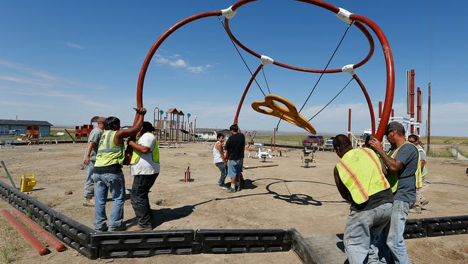 Workers from the Chippewa Cree Tribe install playground equipment with funds from the Washington Redskins Original Americans Foundation on the Rocky Boy's Indian Reservation in Montana.