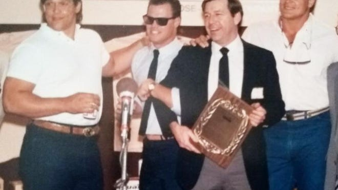 Jim Webb of Bronson holding the plaque surrounded by Steve McMichael, Jim McMahon and Dan Hampton, stars of the Chicago Bears.