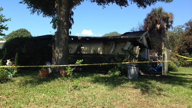 Crime scene tape blocks access to a burned-out house in Titusville after a woman's body was found inside. Police are investigating.