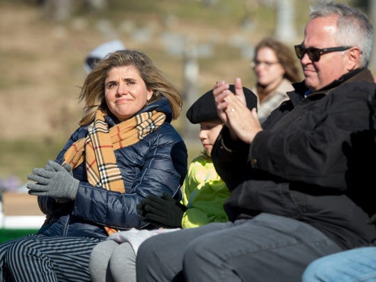 Jenny Bohnert, left, her daughter Elsa Bohnert, 9, and husband Brad Bohnert, listen during the 40th anniversary of the 1977 UE plane crash at Oak Hill Cemetery in Evansville, Ind., on Wednesday, Dec. 13, 2017. Brad's brother Jeff Bohnert was a manager of the UE basketball team and died in the plane crash.