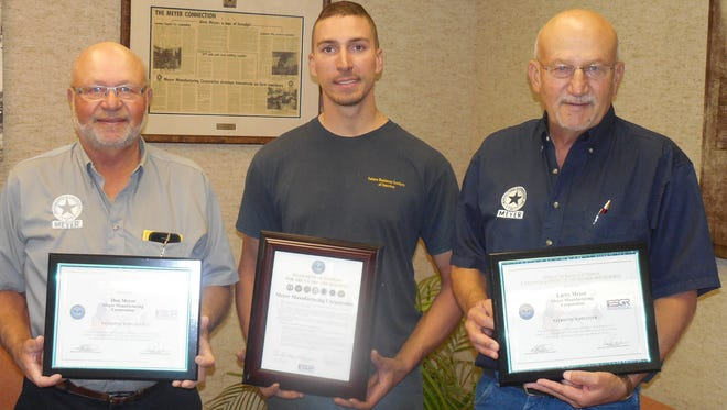 Meyer Manufacturing president Donald Meyer, left, poses with Sgt. Troy Reuth and Meyer Manufacturing vice-president Larry Meyer after presentation of Patriot Award Sept. 19, 2016.