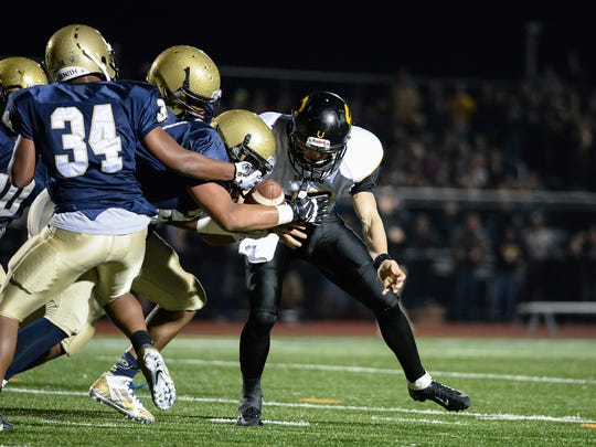 Solanco quarterback Noah McCardell has his handle on the ball stripped by Crusader Tim Kater.