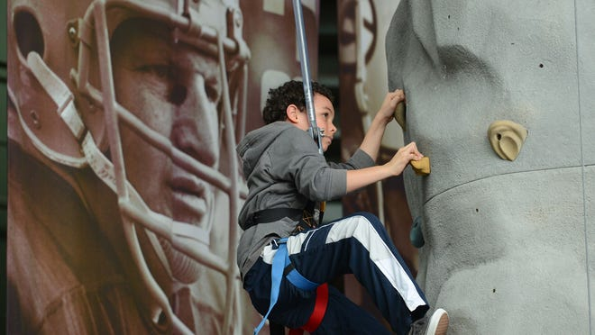Mondes Kelly climbs to the top of the climbing wall Saturday at the NFL Play 60 event at the Lambeau Field Atrium.