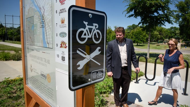 Great River Rotary Club members Eric Reisinger and Alyce Justin talk Thursday, July 6, about the new bike repair station and trail information center recently installed in Lion's Park in Sauk Rapids.