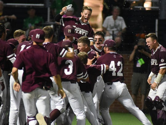 Mississippi State's Elijah MacNamee is swarmed at home after hitting a two-run home run in the ninth inning for a 10-8 win over Vanderbilt in an NCAA college baseball super regional game Friday, June 8, 2018, in Nashville, Tenn. (AP Photo/Mike Strasinger)