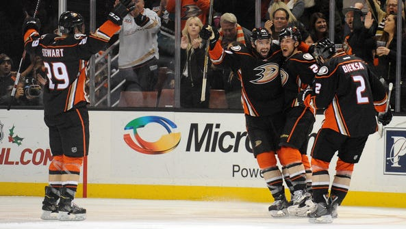 Ducks center Mike Santorelli, middle, is congratulated