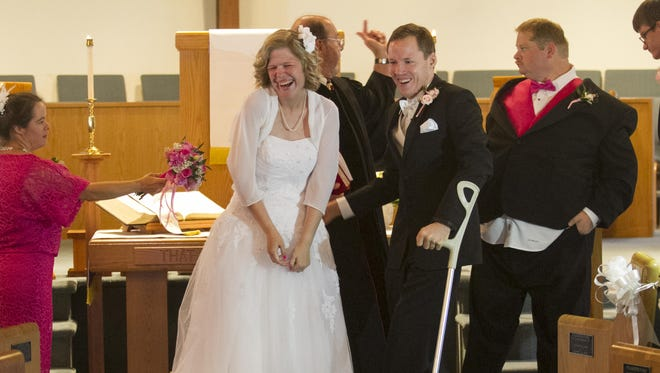 Melissa Kuhlenschmidt laughs shyly after kissing her husband Randy Coleman for the first time during their wedding.