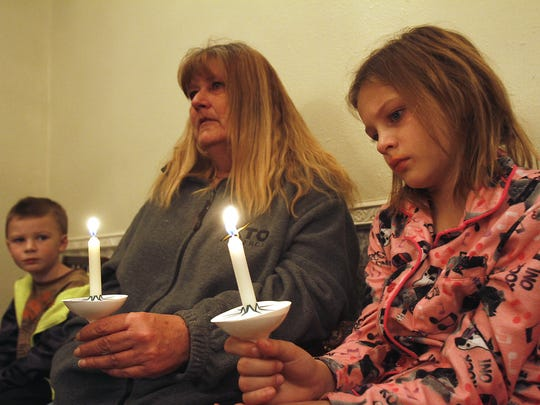 Connor, left, Dewana and Lillian Mae Ingleheart light a cancel in remembrance of Daniel Igleleheart during the Lights of Remembrance event Dec. 12, 2013, at the Brewer Lee and Larkin Funeral Home.