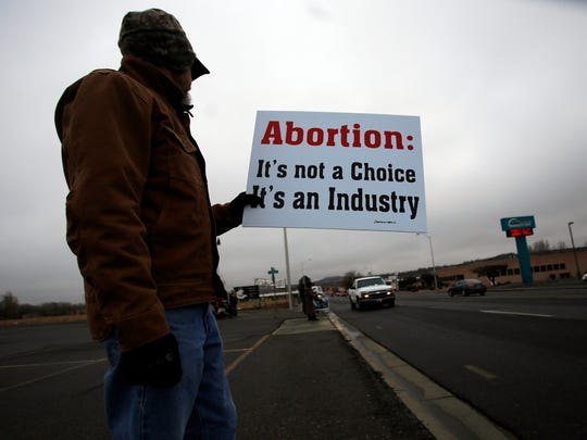 Daryl Firestone holds an anti-abortion sign on Dec. 12 near the 2800 block of East Main Street in Farmington during a protest of Planned Parenthood.