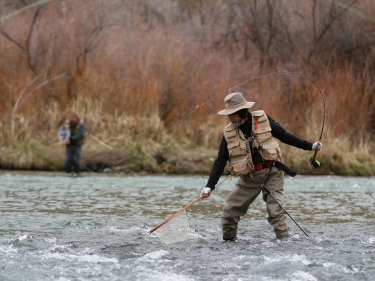 Lorenzo Maldonado, of Albuquerque, reels in a fish on Tuesday at the Texas Hole on the San Juan River at the community of Navajo Dam.