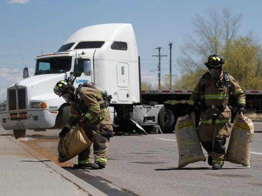 Farmington Fire Department crews clean up a fuel leak after a crash between a semitrailer and a pick-up truck on West Murray Drive between South Auburn Avenue and South Lake Street in Farmington.