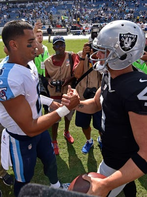 Titans quarterback Marcus Mariota (8) and Raiders quarterback Derek Carr (4) meet at midfield after the game at Nissan Stadium on Sunday, Sept. 10, 2017.