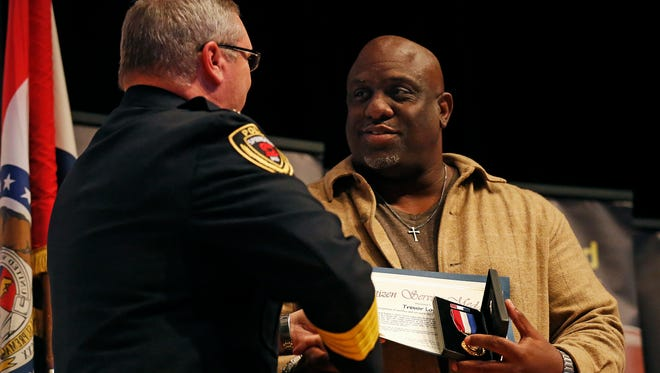 Springfield Police Chief Paul Williams (left) presents Trevor Logan, who along with Terry lambert stopped a rape in downtown Springfield back in August, with service commendations during the annual Springfield Police Department award presentation held at the Springfield Art Museum in Springfield, Mo. on Nov. 17, 2015.