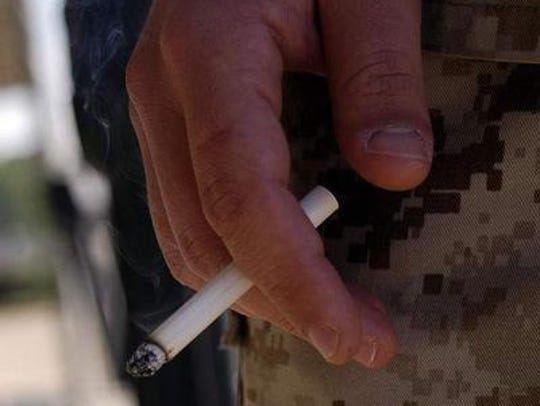 Smoker holds a lit cigarette.