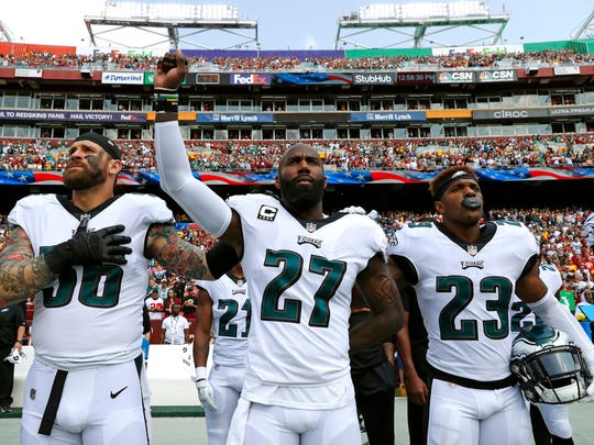 Philadelphia Eagles strong safety Malcolm Jenkins, center, raises his fist as he stands between teammates Chris Long, left, and Rodney McLeod during a rendition of the national anthem before a against the Washington Redskins, Sunday, Sept. 10, 2017, in Landover, Md.