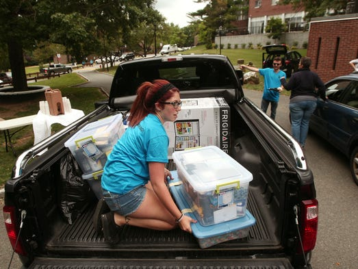 Sophomore Melissa Huskey of Freehold helps unload the car of an incoming freshman as Fairleigh Dickinson University freshman students move into their dorms. They start the Fall 2014 semester next week.,  August 23, 2014, Madison, NJ. Photo by Bob Karp
