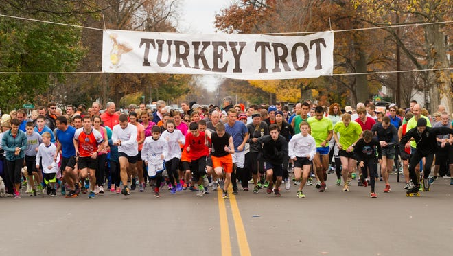 Around 400 runner, walker, skaters, people pushing stroller and people walking their dog take off from South Main Street for the start of the 15th Annual Turkey Trot 5K in Henderson Thursday , Nov. 26, 2015.