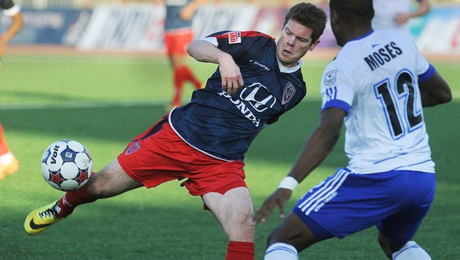The Eleven's Mike Ambersley (left) tries to get a shot off as he is defended by Edmonton's Kareem Moses in the first half of their May 10, 2014, match at Michael A. Carroll Stadium..