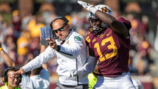 Minnesota Golden Gophers head coach P.J. Fleck and linebacker Jonathan Celestin jump up and celebrate after making a fourth down stop on the goal line in the first quarter against the Maryland Terrapins at TCF Bank Stadium.