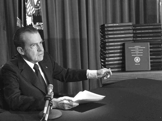 FILE - In this April 29, 1974 file photo, President Richard M. Nixon points to the transcripts of the White House tapes in Washington, after he announced on television that he would turn over the transcripts to House impeachment investigators. The public impeachment inquiry hearings this week usher in a rare and momentous occasion in American history as Congress debates whether to remove a sitting president from office. (AP Photo/File)
