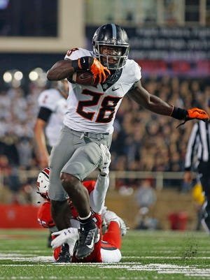 Oklahoma State's James Washington (28) runs the ball down the field during the NCAA college football game against Texas Tech, Saturday, Sept. 30, 2017, in Lubbock, Texas.