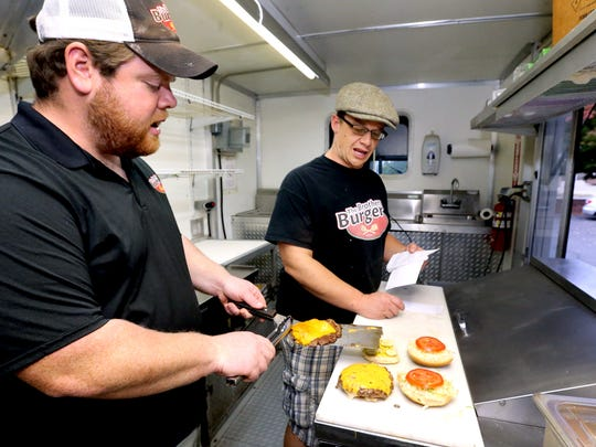 Cole James, left, places hot off the grill burgers onto buns that brother Jeremiah James, right, has dresses in The Brothers Burger food truck on Tuesday, Nov. 8, 2016.