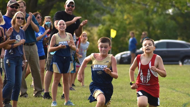 Cheered on by Mercer County fans, Tyce Litwiler, left, charges past Orion's Bridger Burnham during the junior high cross country triangular on Monday, Sept. 14, at Hawthorn Ridge Golf Course, Aledo. Litwiler finished 22nd with a time of 17:46, while Burnham was 23rd at 17:47 for the 2-mile course.