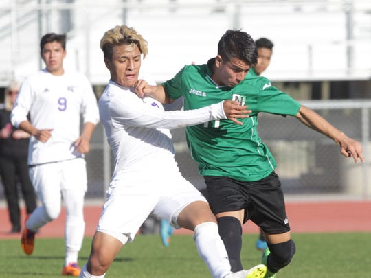 Shadow Hills High School's Jose Hernandez, in white uniform, tries to control possession of the ball against a Nogales High School defender. Shadow Hills won at Indio their CIF match 1-0.